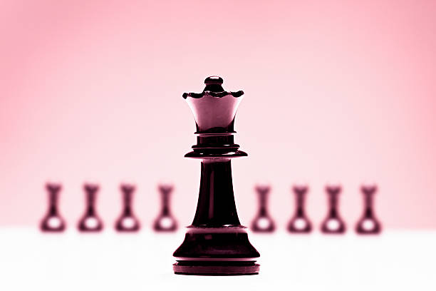 chess queen in front of pawns on pink background - battle of the sexes concept stock pictures, royalty-free photos & images