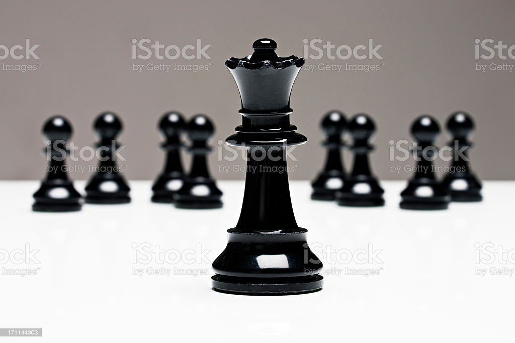 Chess queen stands in front of pawns stock photo
