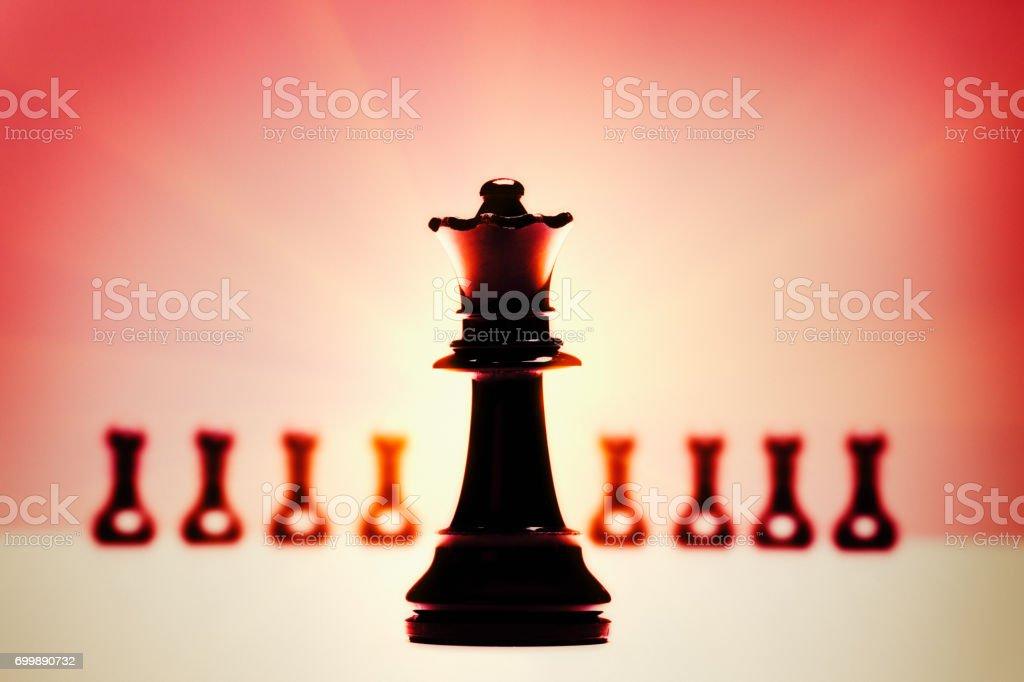 Schach Königin mit defokussierten Bauern in leuchtend rotes Licht – Foto