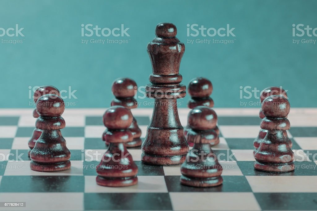Chess team and teamwork concept with wooden chess pieces and chess queen. royalty-free stock photo