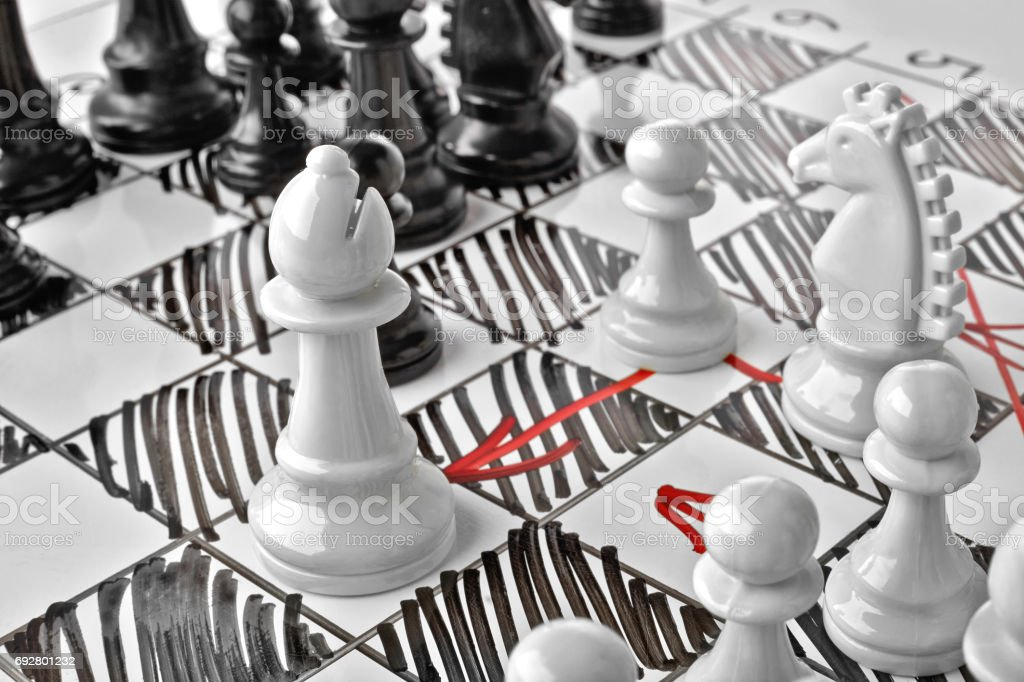 Chess. The white Bishop is under attack. White board with chess figures on it. Plan of battle. stock photo