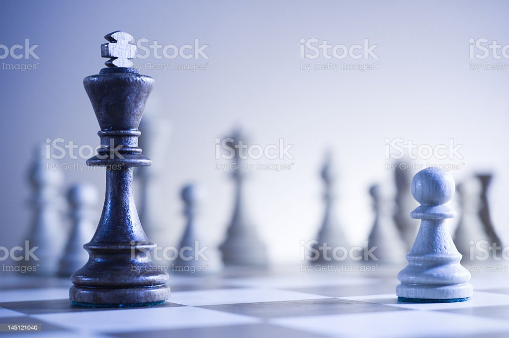Chessboard featuring king and a pawn with blurred background stock photo