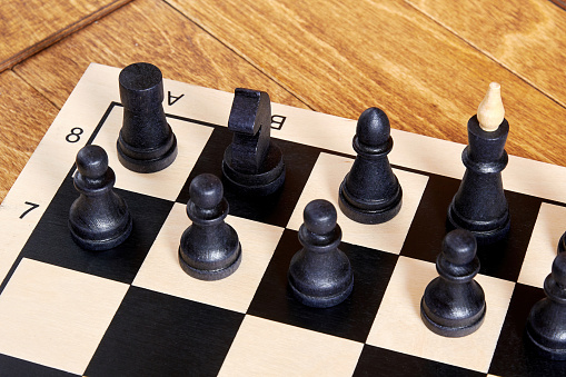 Chessboard with arranged black figures ready to play on the wooden table. Leisure activity and intellectual games