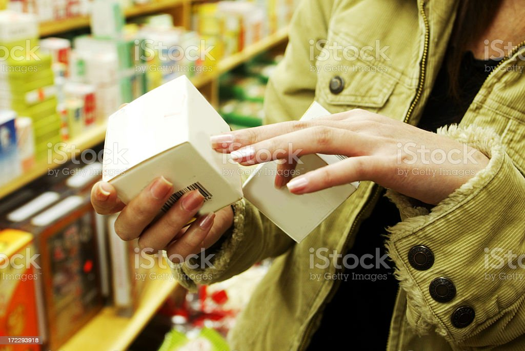 Chest view of a female shopper looking at a cosmetic box royalty-free stock photo