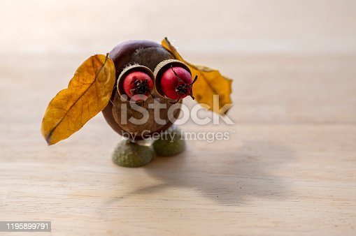 istock Chestnut animal on wooden stump, owl made of chestnut, acorn, yellow leaves and red hawthorn fruits, funny bird 1195899791
