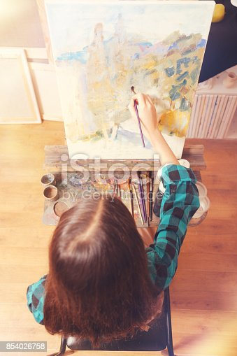 istock Chestnut haired girl painting with oil pants 854026758