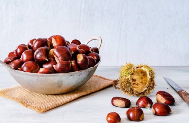 Chestnuts in a metallic basket on rustic wooden background - foto stock