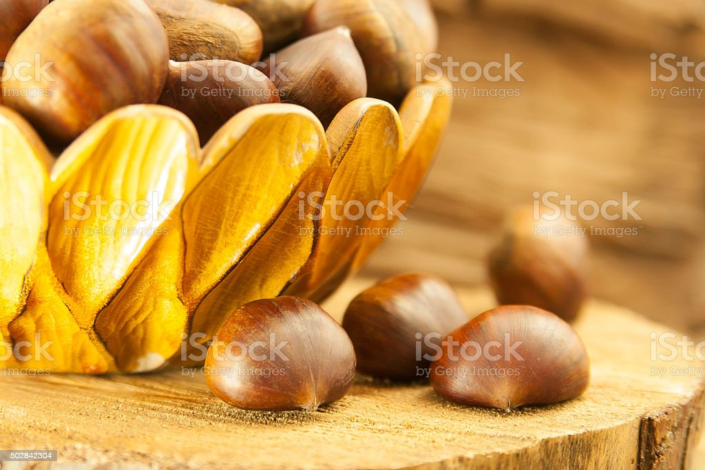 chestnuts in a wooden bowl stock photo