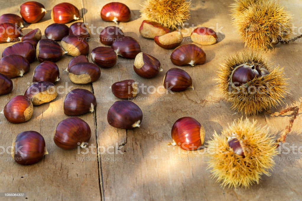 Chestnuts on the old wooden and rustic table. - foto stock