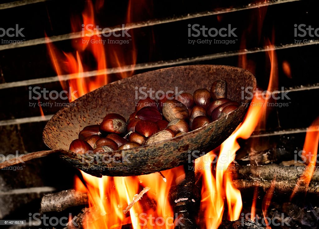 chestnuts roasting in the flames of a log fire stock photo