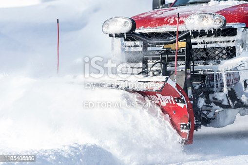 Erskine, USA - March 10, 2019: A Chevrolet 4x4 pick-up truck with an attached blade is plowing deep snow after a Minnesota blizzard.