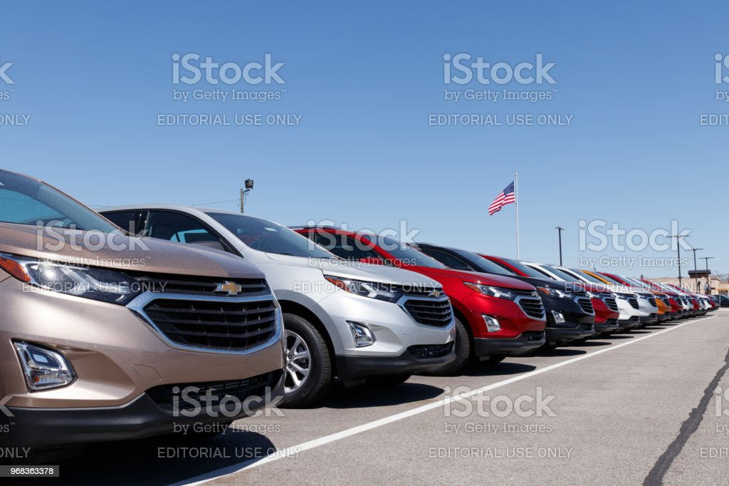 Chevrolet Automobile Dealership with American flag. Chevy is a Division of General Motors stock photo