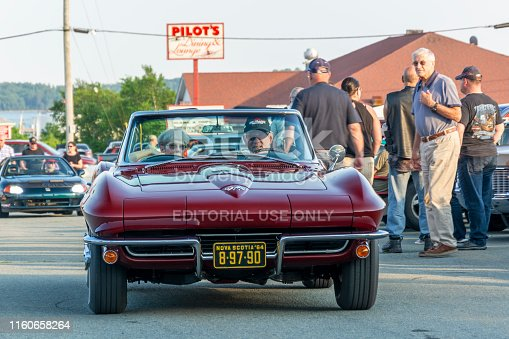 Dartmouth, Nova Scotia, Canada - July 4, 2019 : 1964 Corvette Sting Ray with lady passenger enters the weekly summer A&W Cruise-In at Woodside ferry terminal parking lot. A man watches the classic sports car drive by as people walk among the many classic cars on display.