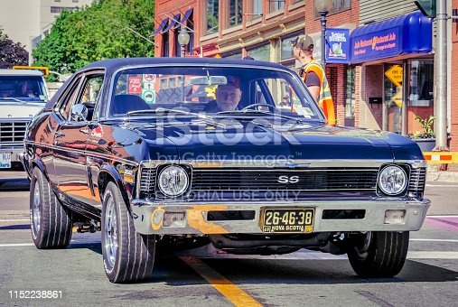 Moncton, New Brunswick, Canada - July 7, 2017 : Man drives his 1969 Chevrolet Nova SS in downtown area of Moncton, New Brunswick during 2017 Atlantic Nationals Automotive Extravaganza.