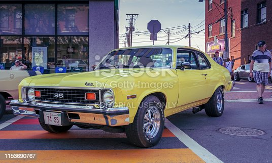 Moncton, New Brunswick, Canada - July 7, 2017 :  2017 Atlantic Nationals Automotive Extravaganza, 1974 Chevrolet Nova SS on display in the downtown area of Moncton, New Brunswick. Man walking behind the Chevy gives it a glance.