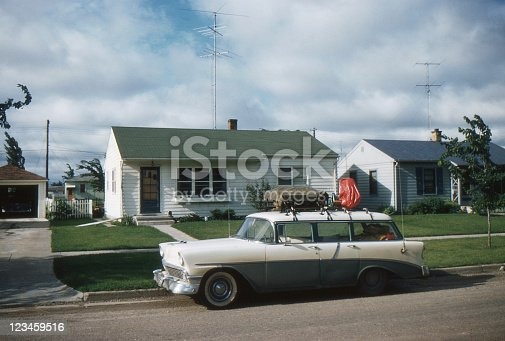 1956 Chevrolet station wagon packed for vacation in front of new tract house with TV antenna. Symbols of the affluent post WWII society in USA. Waterloo, Iowa, 1957. Kodachrome scanned film with grain.