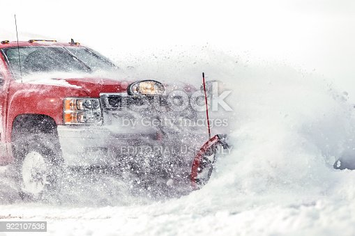 Fosston, USA - February 18, 2018: A red Chevrolet 4x4 pickup truck with a blade is plowing fresh powder snow after a winter snowstorm in northern Minnesota.