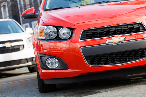 Halifax, Nova Scotia, Canada - December 13, 2011: At a car dealership, a 2012 Chevrolet Sonic front view with another Chevrolet compact vehicle behind.  Price tag in front window partially visible.  The Sonic replaced the Chevrolet Aveo in North America and was met with a much stronger market appeal.  The revised headlights, larger wheels, revised interior, and overall more aggressive design makes the Sonic a welcome replacement to the bland Aveo.