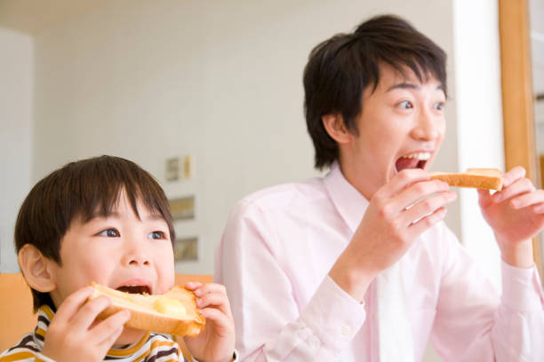 Chewing a toast to Dad and boy Chewing a toast to Dad and boy ASAP stock pictures, royalty-free photos & images