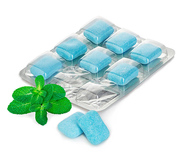 Chewing gum in blister with mint leaves close-up. stock photo