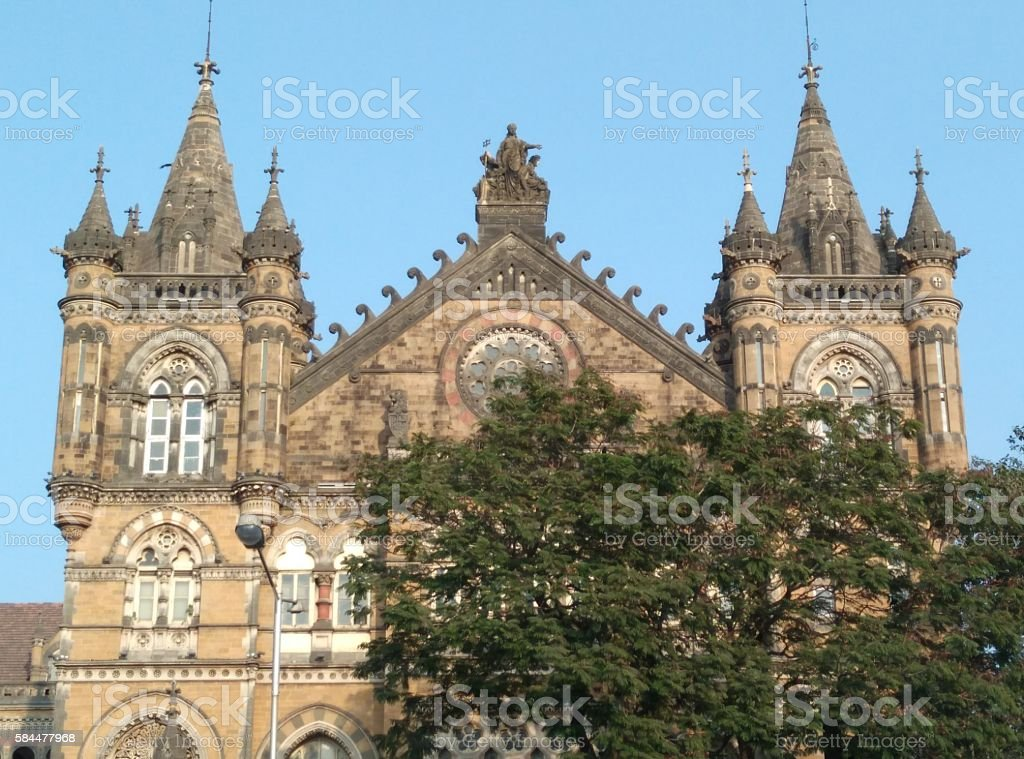 Chhatrapati Shivaji Terminus Railway Station Early morning shot of Chhatrapati Shivaji Terminus Railway Station of Mumbai, India, previously known as Victoria Terminus. The architecture design has influences from Victorian Italianate Gothic Revival architecture and traditional Mughal buildings. The station is surrounded by tress perfectly balancing natural and artistic aesthetics. Architecture Stock Photo
