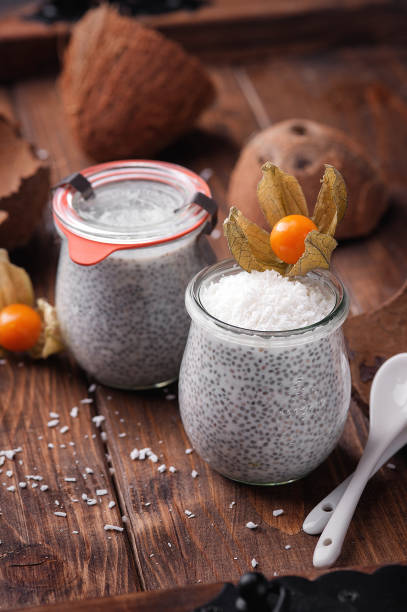 chia pudding auf kokosmilch mit physalis verziert. - chia pudding kokosmilch stock-fotos und bilder