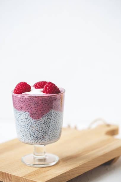 pudding de chiches au lait d'amande, yaourt, poudre de pitaya et framboises. concept végétalien. - pudding au lait roses photos et images de collection