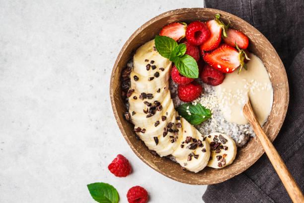 chia pudding med bär, banan, jord nöts smör och kakao nibs i kokos skal skål, uppifrån. - stålpenna bildbanksfoton och bilder