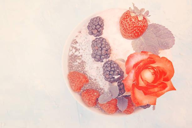 pudding de clerbois avec baies. dessert avec clerbois, framboises, bleuets, crème fouettée et de fraises. concept de nourriture super saine de désintoxication. - pudding au lait roses photos et images de collection