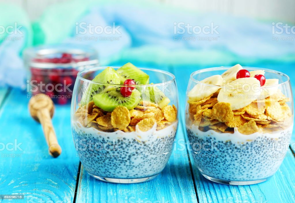 chia pudding with corn flakes and fruits on blue wooden background stock photo