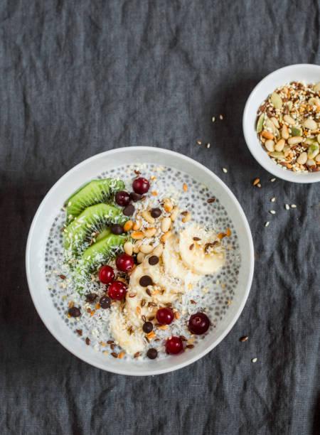 chia pudding mit früchten, samen und nüssen auf einem dunklen hintergrund, ansicht von oben. gesundes frühstück oder snack - chia pudding kokosmilch stock-fotos und bilder