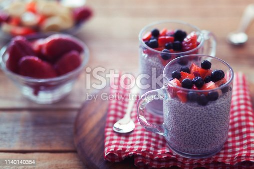 Chia pudding with strawberries and chokeberry, served in glasses, close-up