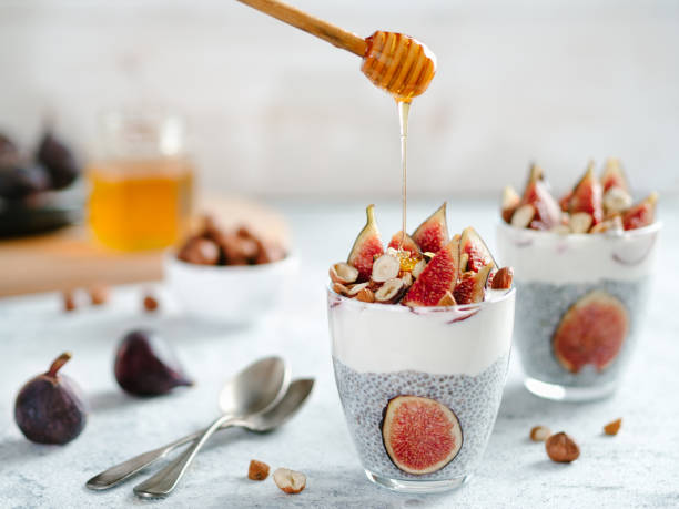 chia pudding with yogurt, figs, nuts, honey Healthy chia pudding with yogurt, figs and nuts in glass. Ideas and recipes for healthy breakfast, snack or dessert. Honey drips into glass with chia seeds pudding. Copy space for text. pudding stock pictures, royalty-free photos & images