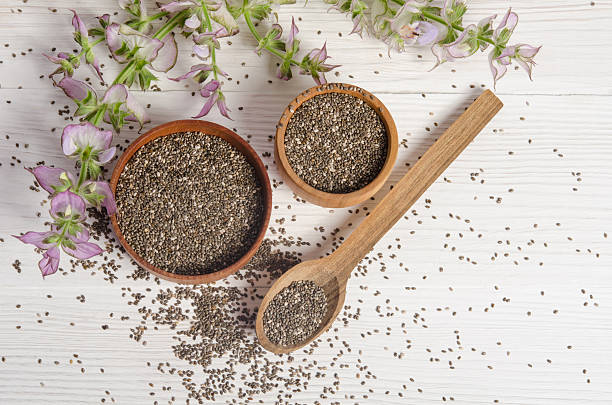 chia seed healthy super food with flower over white - chia seed stock photos and pictures