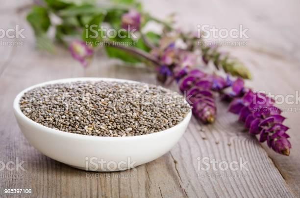 Foto de Chia Sementes Saudável Superalimento Em Tigela Com Flor Sobre A Mesa De Madeira e mais fotos de stock de Alimentação Saudável