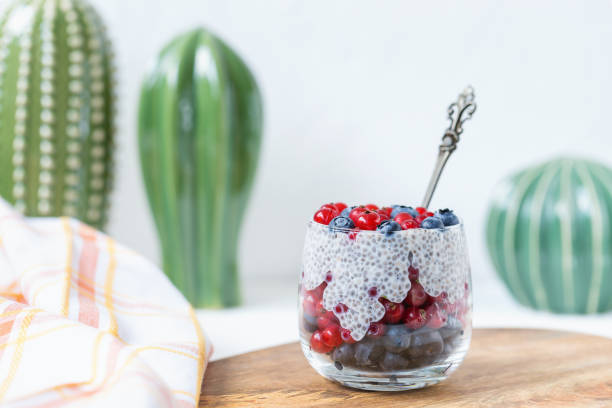pudding de graine de avec des myrtilles et des baies de groseille rouge dans un verre - pudding au lait roses photos et images de collection