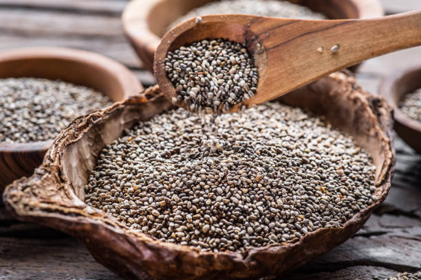 Chia seeds in wooden spoon over organic dish with chia seeds on old wooden table. stock photo