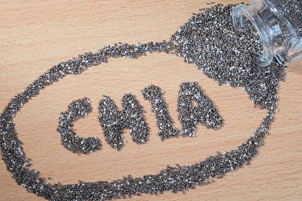 chia palabra de semillas de chia que el vertido en placa de madera - foto de stock