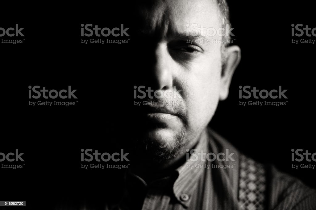 Chiaroscuro portrait of a mean looking man stock photo
