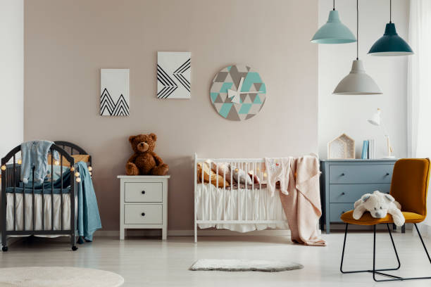 Chic baby bedroom with wooden cribs, lamps, white wooden nightstand with brown teddy bear and fashionable yellow chair Chic baby bedroom with wooden cribs, lamps, white wooden nightstand with brown teddy bear and fashionable yellow chair crib stock pictures, royalty-free photos & images