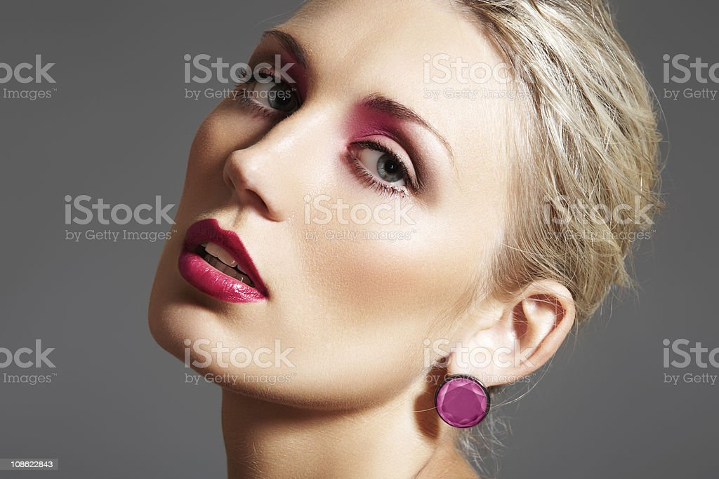 Chic beauty with evening make-up, bright lips and pink jewelry stock photo
