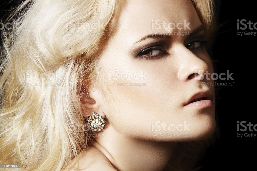 Chic frown model with diamond jewelry, blond hair stock photo