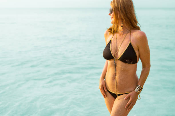 chic woman in black bikini and jewelry by the sea - older women bikini stock pictures, royalty-free photos & images