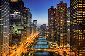 Downtown city buildings and skyline over the Chicago River at night in Illinois USA
