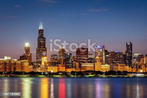 Illuminated Cityscape, Skyline of Chicago at Twilight, Night. Modern urban skyscraper lights mirroring in the Lake Michigan water. Long Exposure. Chicago, Illinois, USA.