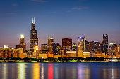 Illuminated Cityscape, Skyline of Chicago at Twilight, Night. Modern urban skyscraper lights mirroring in the Lake Michigan water. Long Exposure. Chicago, Illinois, USA.