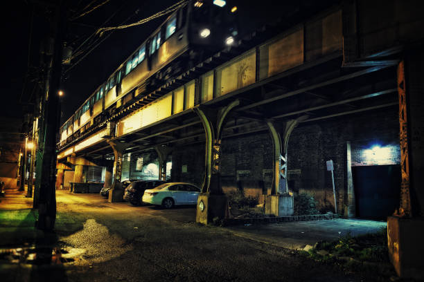 A Chicago CTA city subway train going over a bridge in a dark urban alley at night. stock photo