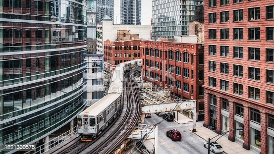 Chicago typical silver colored commuter cta train moving on elevated tracks to railroad station in between urban chicago city buildings. Panorama Shot. Chicago, Illinois, USA, North America.
