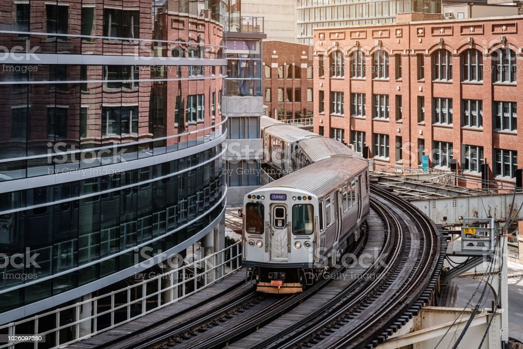 Chicago CTA Train between City Buildings Chicago typical silver colored commuter train moving on elevated tracks to railroad station in between urban city buildings of Chicago, Illinois, USA. American Culture Stock Photo