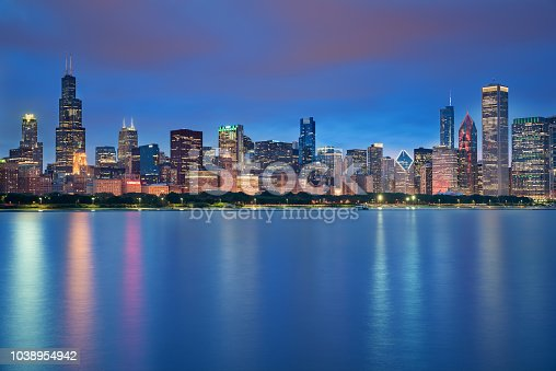 Chicago downtown skyline taken in a fantastic cloudy evening, with lights of the skyscrapers reflected in lake Michigan,  Illinois, United States